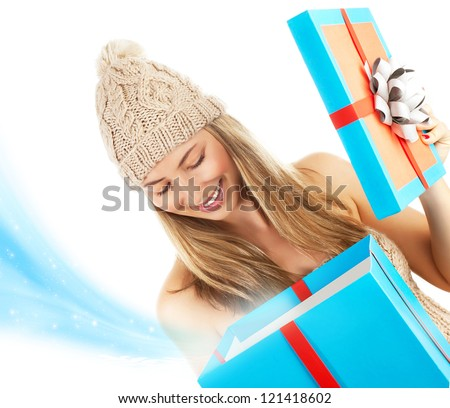 Photo of pretty blond woman in stylish winter hat opening big blue present box, beautiful girl receive Christmas gift, happy young lady holding magic giftbox isolated on white background, New Year eve - stock photo