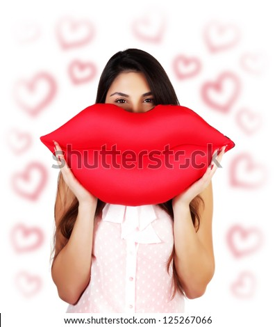 Photo of pretty brunette woman holding in hands big red lips, soft pillow-toy kiss-shaped, happy female having fun, isolated on white background with red heart shapes, Valentine day, love concept - stock photo