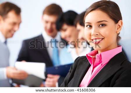 Photo of pretty business leader looking at camera in working environment