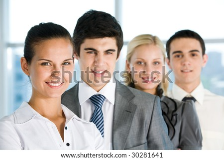 Photo of pretty female looking at camera with her colleagues behind