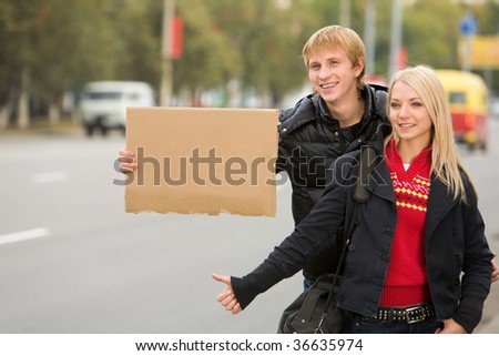 Photo of pretty girl and handsome guy hitchhiking on city road