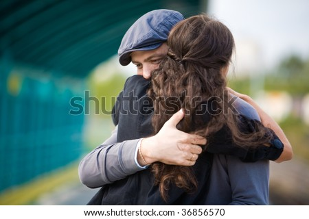 Photo of pretty girl and her boyfriend embracing during seeing off - stock photo