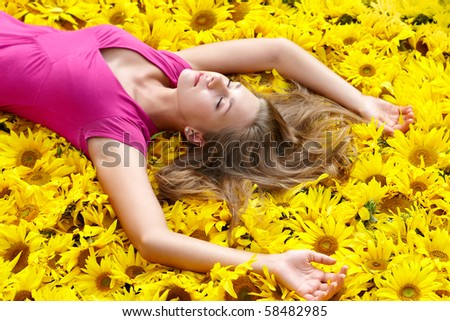 Photo of pretty girl lying on sunflowers and having pleasure - stock photo
