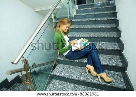 Photo of pretty girl sitting on stairs and making notes in copybook - stock photo