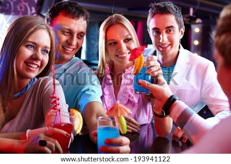 Photo of pretty girls and smart guys looking at barman at party - stock photo