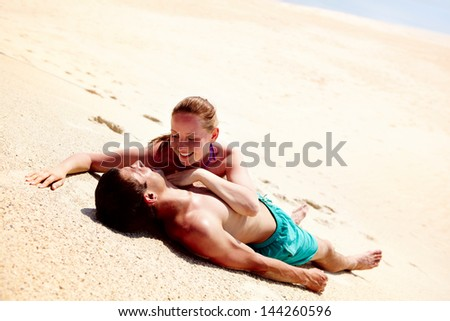 Photo of pretty woman looking at her husband while both lying on sand - stock photo