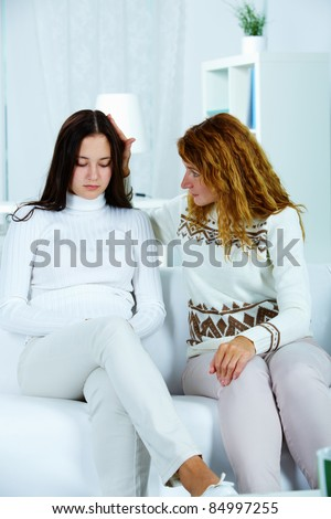 Photo of pretty woman reassuring her sad daughter - stock photo