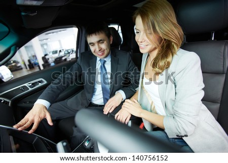 Photo of pretty woman sitting in car and listening to salesman in automobile center - stock photo