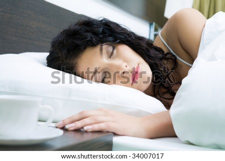 Photo of pretty woman sleeping peacefully in white linens - stock photo