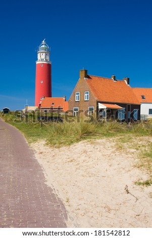 Photo of red classic lighthouse at the beach  - stock photo