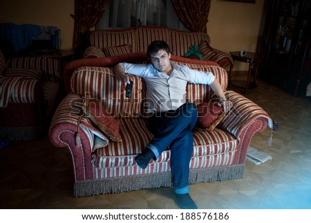 Photo of relaxed man watching TV at living room at night - stock photo