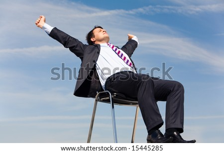 Photo of relaxing businessman sitting on chair and stretching himself on background of blue sky - stock photo