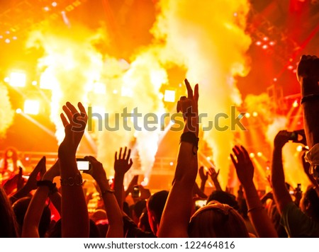 Photo of rock concert, music festival, New Year eve celebration, party in nightclub, dance floor, disco club, many people standing with raised hands up and clapping, happiness and night life concept - stock photo