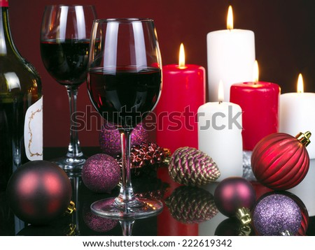 Photo of romantic Christmas dinner, glass of red wine, beautiful little candle, holiday table setting, New Year decorations on a mirrored table with red background - stock photo