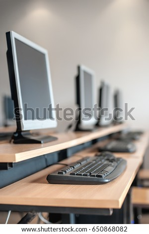 Photo of row computers in classroom or other educational institution. Close up