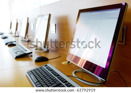 Photo of row of computers in classroom of college or other educational institution - stock photo