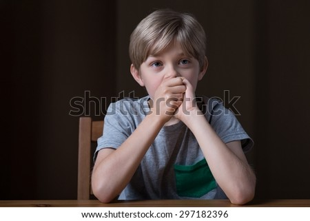 Photo of sad young boy covering mouth with hands - stock photo