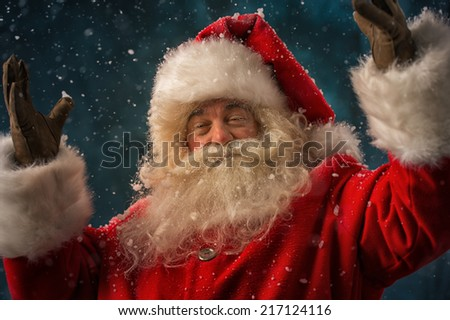 Photo of Santa Claus outdoors under blowing wind and falling snow and looking at camera - stock photo