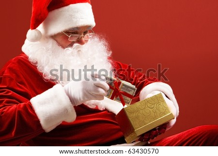 Photo of Santa Claus putting pack of dollars into small giftbox - stock photo