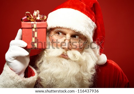 Photo of Santa Claus with giftbox looking at it while keeping it by his ear