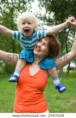 Photo of screaming boy sitting on mother shoulders - stock photo