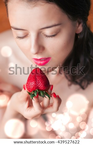 Photo of seductive female eating strawberry, close up portrait of sensual woman biting juicy fruit , fruity diet, tasty dessert, Valentine day, pleasure concept - stock photo