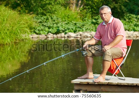 Photo of senior man fishing on weekend in the country - stock photo