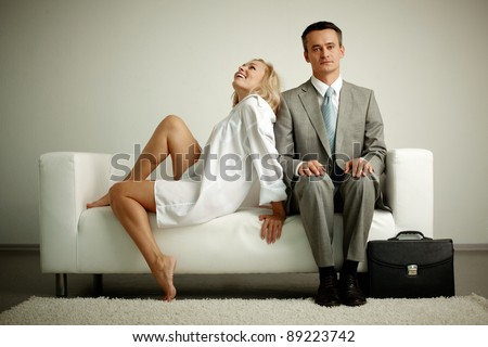 Photo of serious man in suit sitting on sofa with seductive laughing woman near by - stock photo