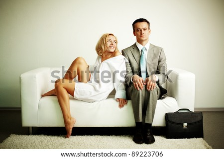 Photo of serious man sitting on sofa with happy seductive woman looking at him - stock photo