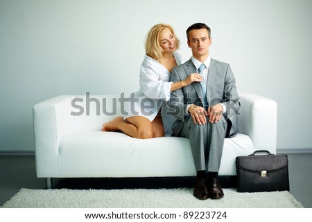 Photo of serious man sitting on sofa with seductive woman holding him by tie - stock photo