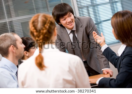 Photo of several employees discussing something with focus on their leader - stock photo