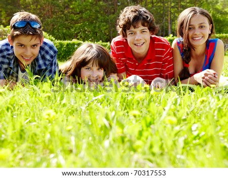 Photo of several happy friends lying on green lawn outdoors - stock photo