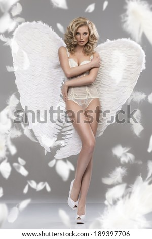 Photo of sexy blonde woman with long hair wearing angel's wings. Beautiful body.  - stock photo