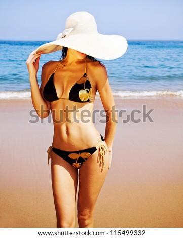 Photo of sexy woman on the beach, attractive female wearing black seductive swimsuit and big fashionable hat, healthy slim girl stand on coastline, summer holidays, luxury resort, vacation concept - stock photo