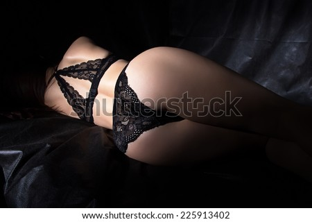 Photo of sexy woman's buttocks on black background - stock photo