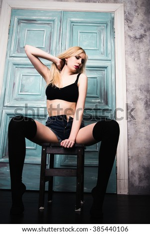 photo of Sexy young blonde woman posing on stool