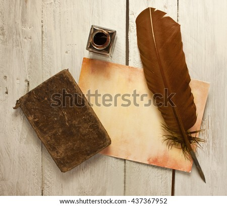 Photo of sheet of aged paper with quill pen, bottle of ink, and old notebook, shot from above on wooden background texture, slightly toned; concept of studying or writing; vintage objects - stock photo