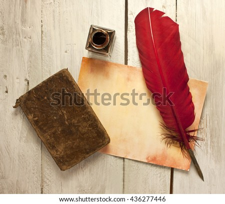 Photo of sheet of aged paper with quill pen, bottle of ink, and old notebook, shot from above on a wooden background texture, slightly toned; concept of studying or writing; vintage objects - stock photo