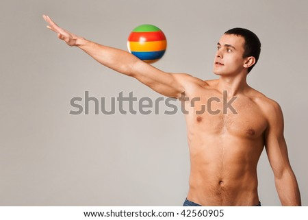 Photo of shirtless man looking at ball rolling down his stretched arm - stock photo