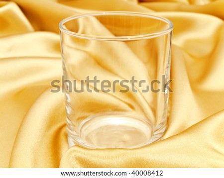 photo of single glass at golden drapery background