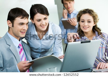 Photo of sitting businessman looking at laptop monitor while confident woman near by pointing at its screen