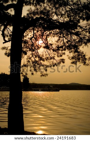 Photo of sky with sunset, tree and surface of water