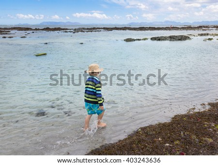 Photo of small boy walking through the shallow sea water next to washed up sea weed