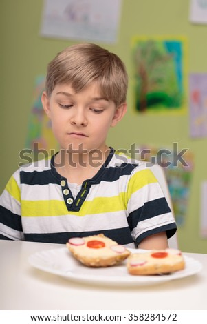 Photo of small picky eater boy dislike healthy breakfast - stock photo