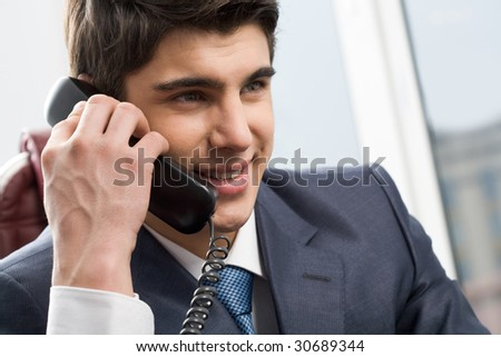 Photo of smart businessman calling somebody and smiling during communication