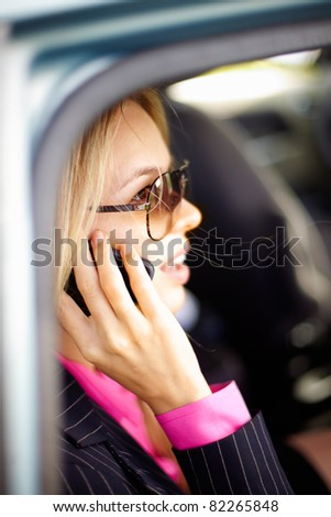 Photo of smart businesswoman talking by mobile phone in a car - stock photo