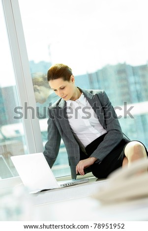 Photo of smart businesswoman working with laptop in office
