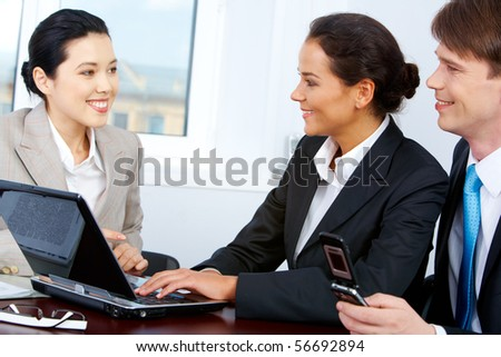 Photo of smart partners interviewing pretty Asian female in office - stock photo