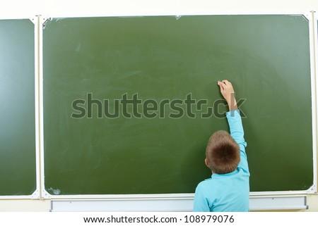 Photo of smart pupil going to write something on blackboard - stock photo