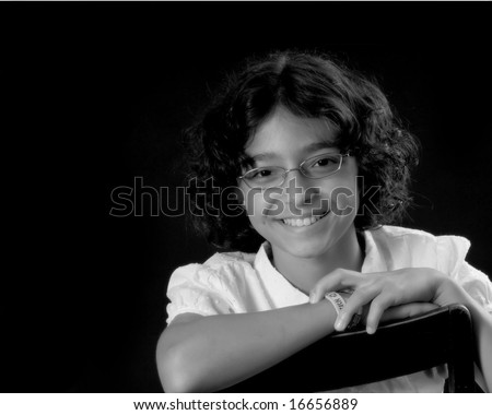photo of smart young teenage girl with arms folded on chair - stock photo